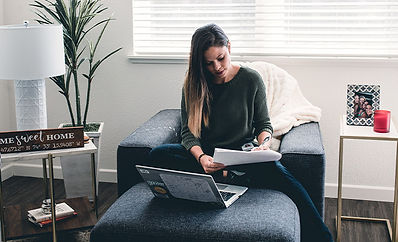 Woman working on a laptop from a comfy chair