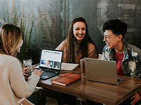 Young adults laughing at a table