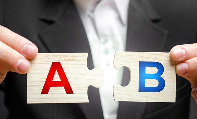 businessman putting a and b together in a jigsaw format