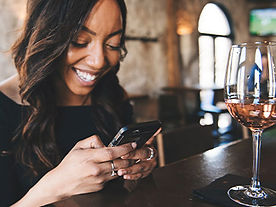 young woman at the bar looking at her mobile with a half drunk glass of wine
