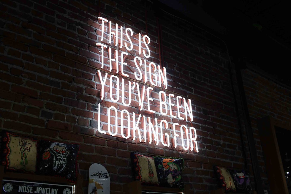 Sign on top of bar on a brick wall
