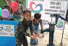 Young Indian boy splashing water from a newly built water well.
