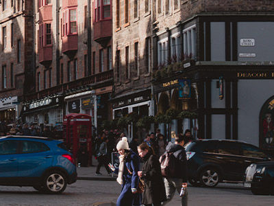 Long shot of UK High street with cars and pedestrians