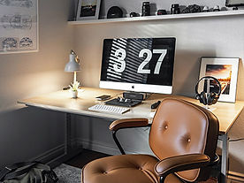 home office set with large pc moniter and a 70's inspired leather chair