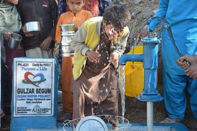 Young boy playing with a water well in Pakistan