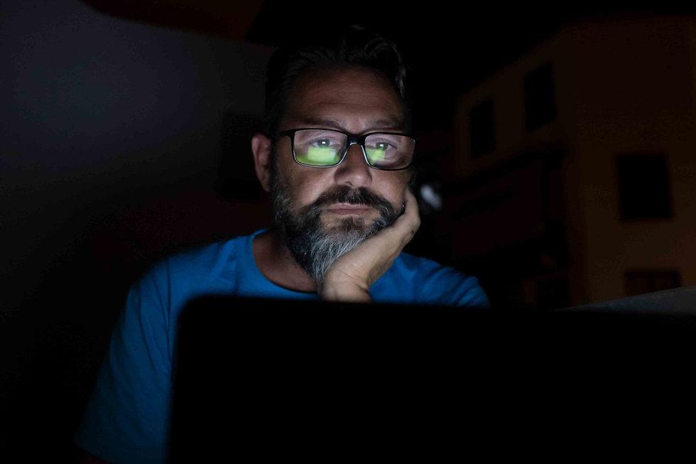 Man looking at pc checking his social media