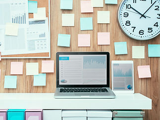 Laptop and folders on a shelf in the office, pinboard on the background, business workspace and technology