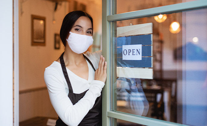 Waitress stood at door with mask welcoming people back in
