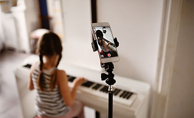 Girl recording piano playing on mobile phone