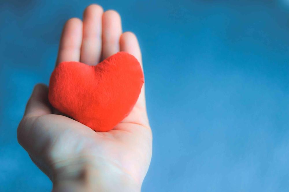 Hand holding a felt heart against a blue background