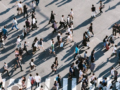 Long shot of a crowd of people crossing the street