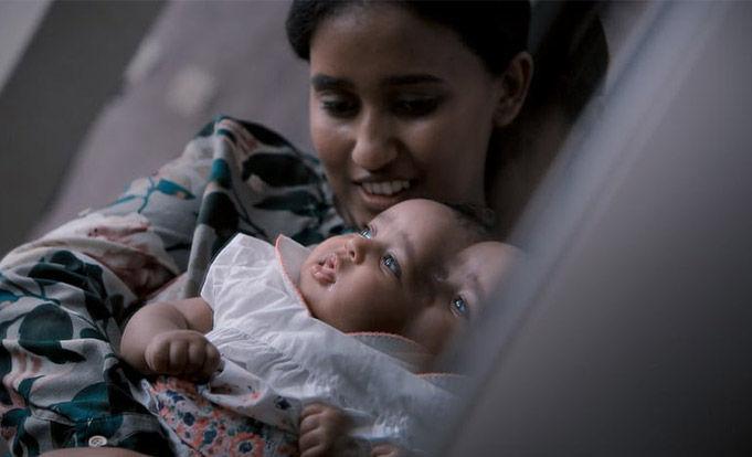 New mum holding little baby in white