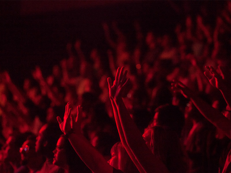 Close up picture of a crowd bathed in red light