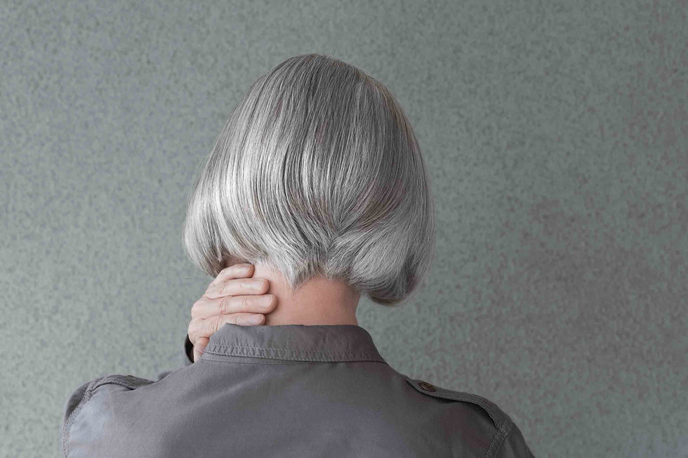woman with gray hair faced towards wall