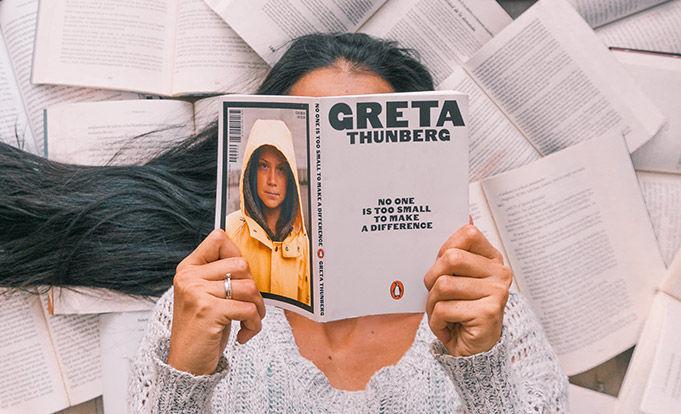 Woman with Black hair holding a Greta Thunberg book.
