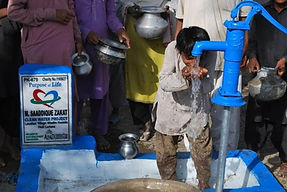 Young boy receiving water from a newly donated water well