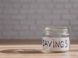 Empty jar on a table with the word Savings stuck to the glass