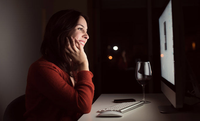 Woman in front of Video call with glass of wine
