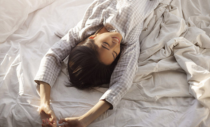 Woman stretching after having a nap in bed
