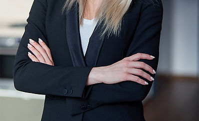 Nice and calm blond, middle-age businesswoman standing at her office. Looking at camera. She wearing a black formal suit and white t-shirt.