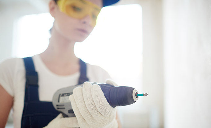 Young woman working a drill