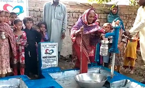 Woman collecting water from new water well in pakistan built by Purpose of Life Charity
