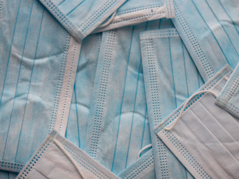 A large collection of light blue surgical face masks that cover the picture.