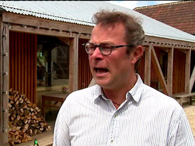 Hugh Fearnley-Whittingstall talking to an interviewer with a farm in the background