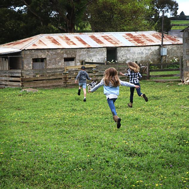 Kids airborne running through paddock.jp