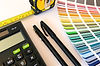 Tools of the trade featuring a measuring tape, calculator, pens, drawing pad and fan of colour swatches