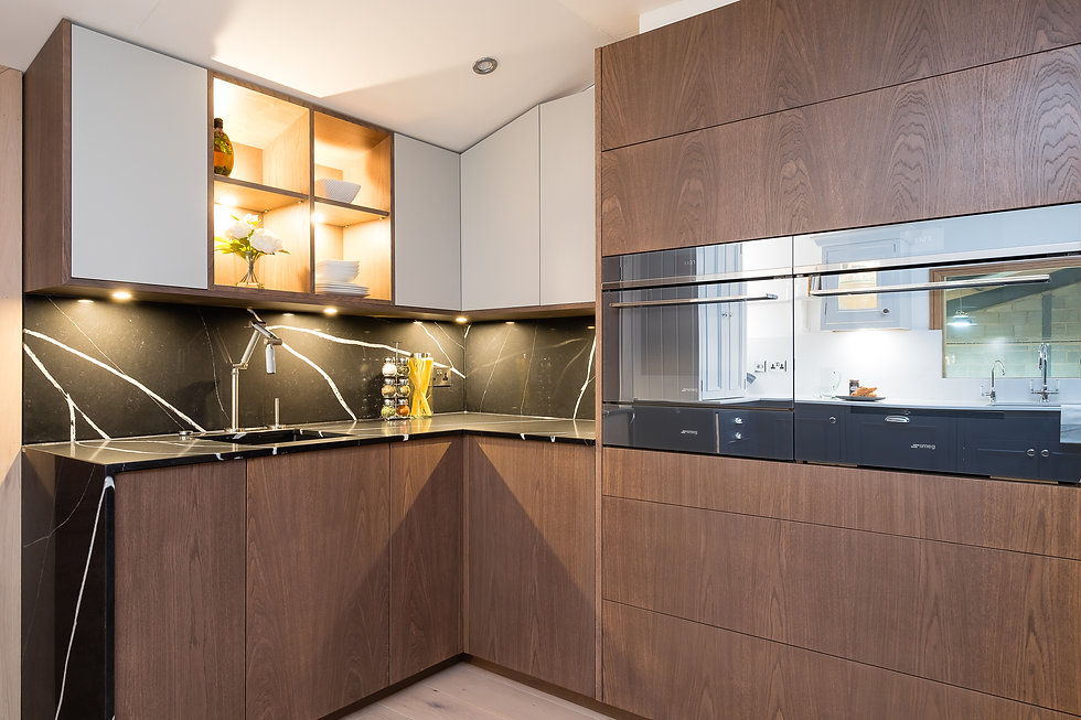 A handmade push-to-open kitchen design inspired by a German kitchen. Complete with white wall cabinets and walnut veneered bottom cabinets, integrated appliances and under cabinet lighting