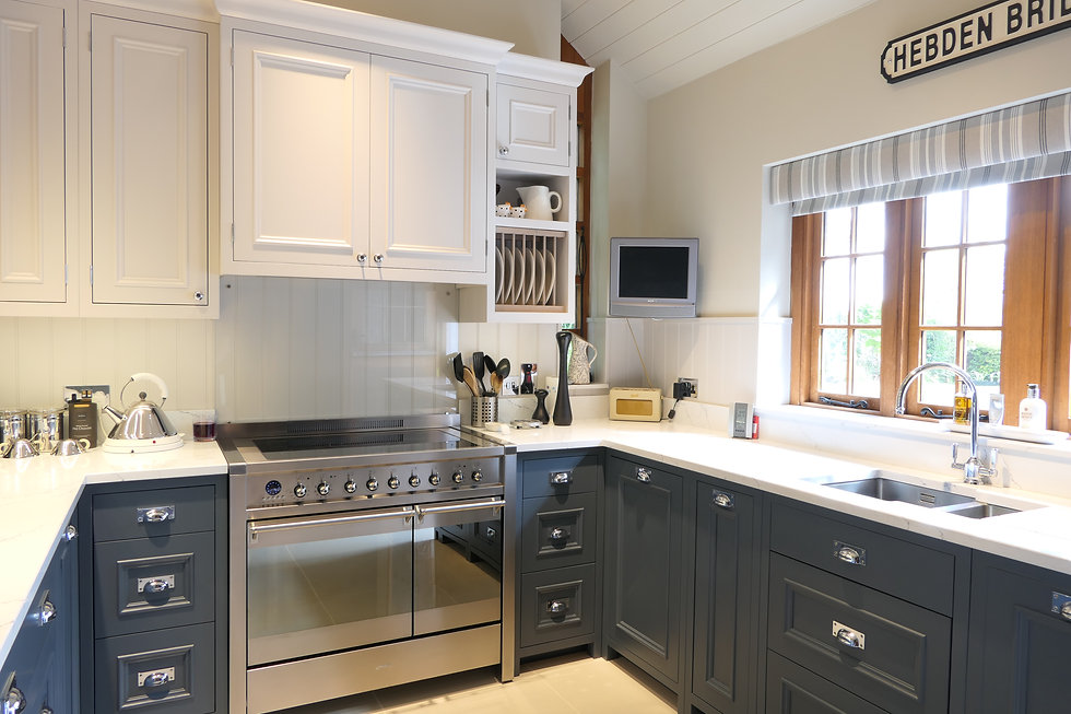 A blue and white handmd kitchen featuring a deorative bolection moulding on the doors and drawers.