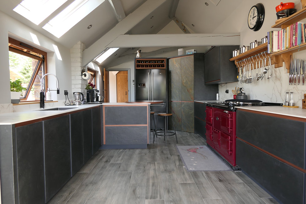 Overview of a slate veneered pull to open handmade kitchen with a copper frame
