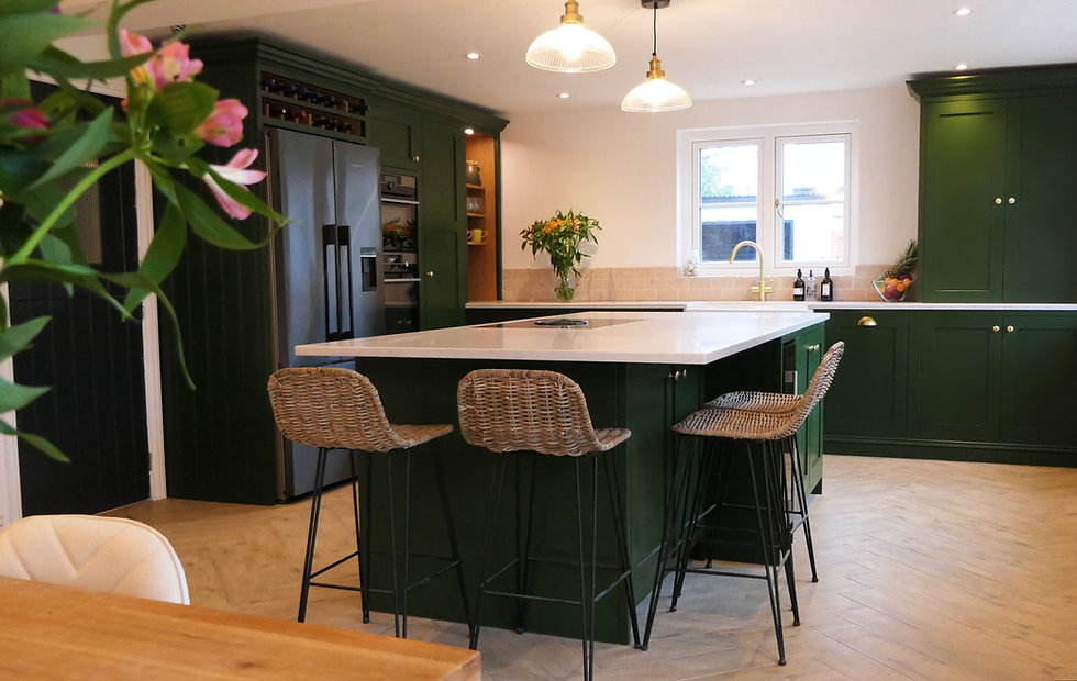 Overview of green handmade kitchen with white worktop and brass handles