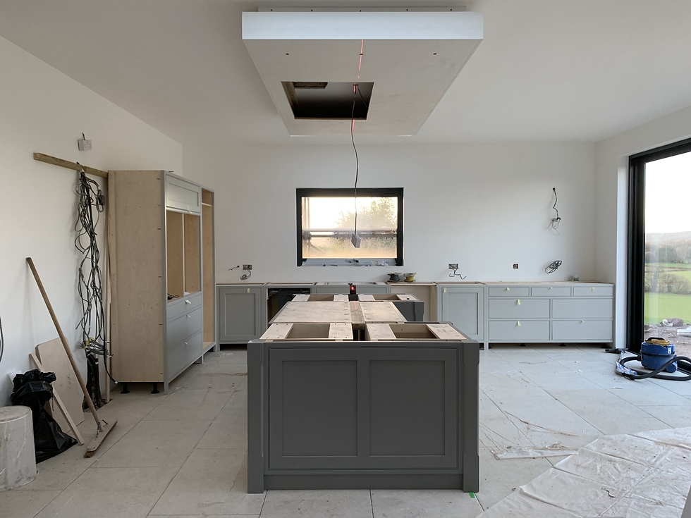 A light grey kitchen with dark grey kitchen island being fitted into our clients property