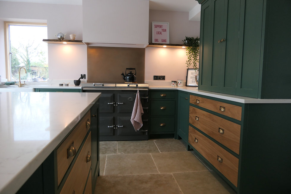 A green handmade kitchen with natural oak drawers and an everhot cooker