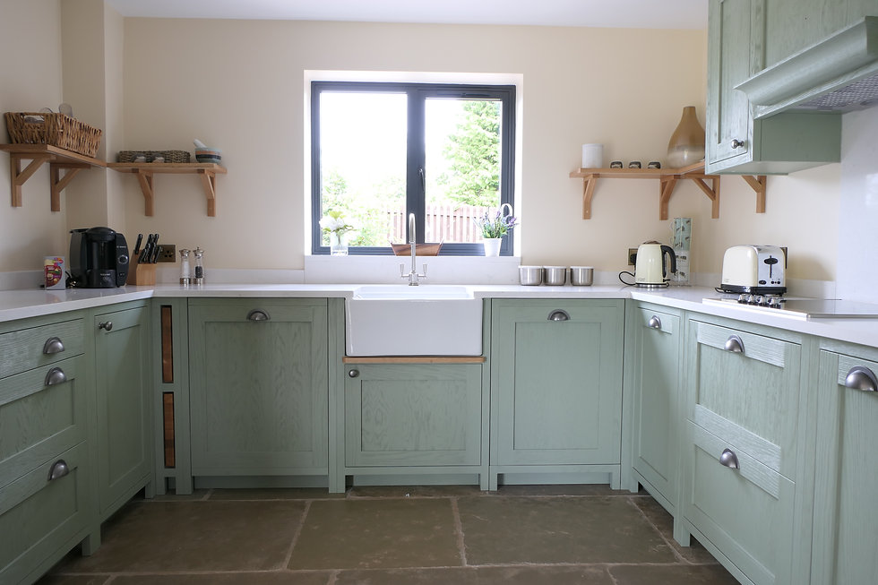 A light green kitchen with a deep grain stain to show off the wood grain, with push to open chopping boards