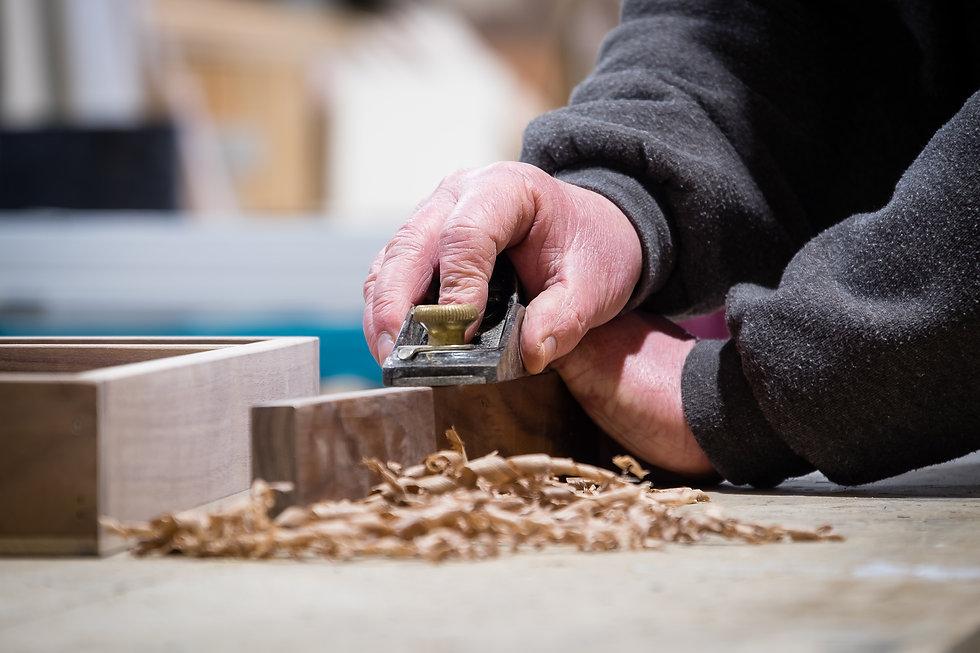 A worker plaining wood