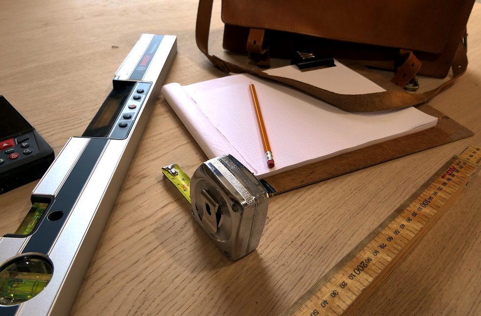 Tools of the trade featuring a laser measure, measuring tap, sketch pad with pencil, ruler and bag