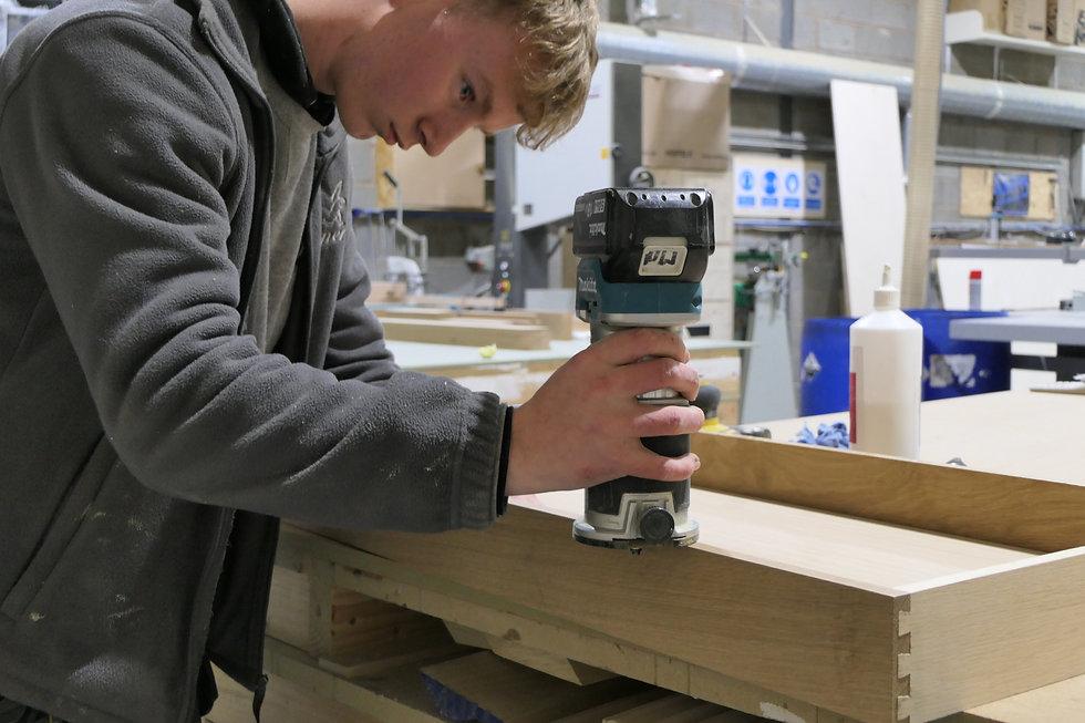 An employee sanding a drawer box