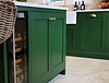Close up of green handmde kitchen withintegrated wine cooler and decorated with brass handles