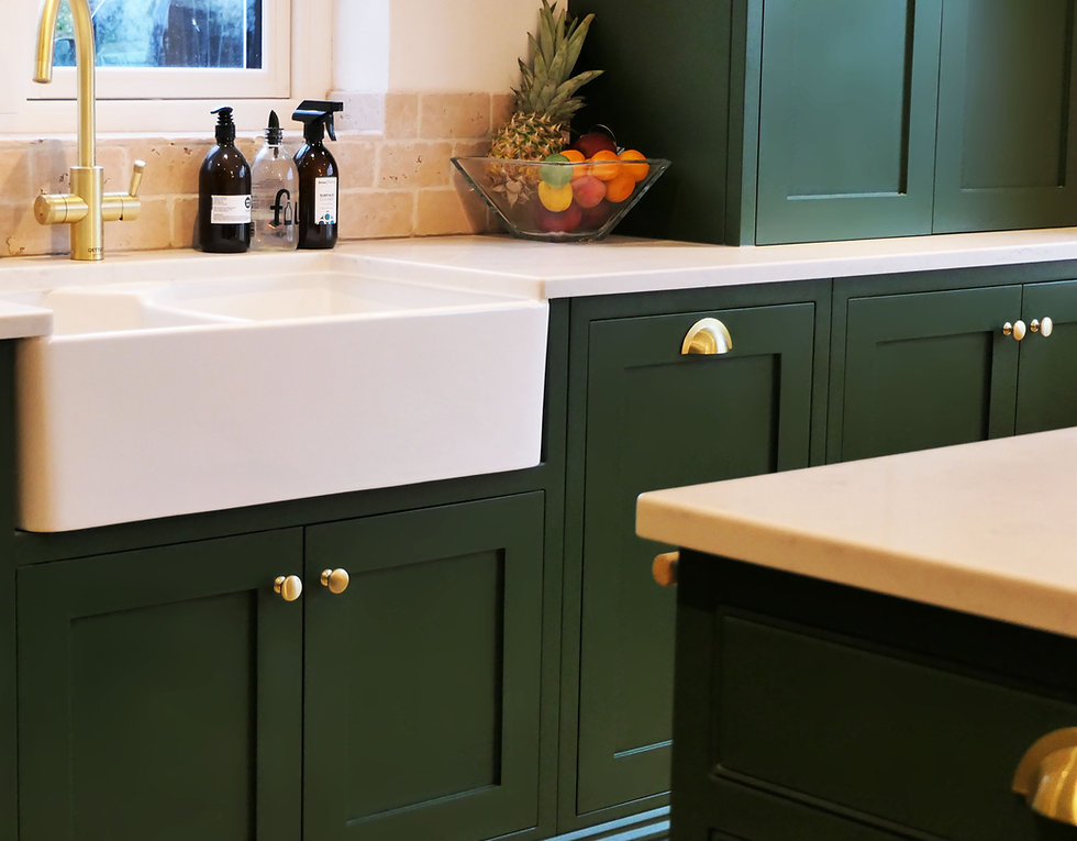 Run of green cabinetry featuring a blefast sink and brass handles