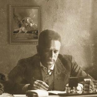 Kadri Cakrani working at his desk, with a painting of Albanian warrior Skanderbeg behind him.