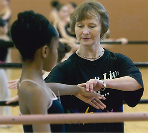 : Bolshoi Ballet Academy teacher Syrova correcting a young female dancer's arm placement in second position at the barre.