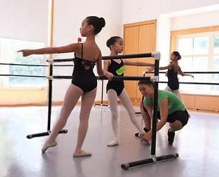 Bolshoi Ballet Academy Teacher Yevgeniya Kazeeva correcting the placement of a female dancer's foot in tendu devant at the barre