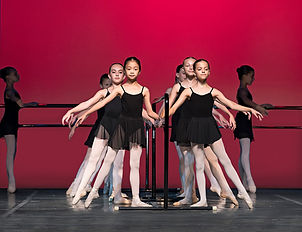 Young dancers in black leotards and wrap skirts at the barre in tendu à la seconde.