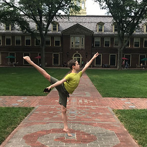 Bolshoi Ballet Academy Summer Intensive male participant posing in first arabesque in a courtyard at the Loomis Chaffee School.