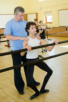Bolshoi Ballet Academy teacher Mikhail Sharkov corrects the placement of David Soares's shoulders at the barre.