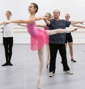 Bolshoi Ballet Academy teacher Georgii Gusev partners a dancer in fourth arabesque en pointe.