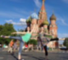 Two female NSLI-Y participants posing in first arabesque in front of Saint Basil's Cathedral in Moscow.